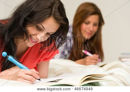 Young teenage girls lying and studying on bed