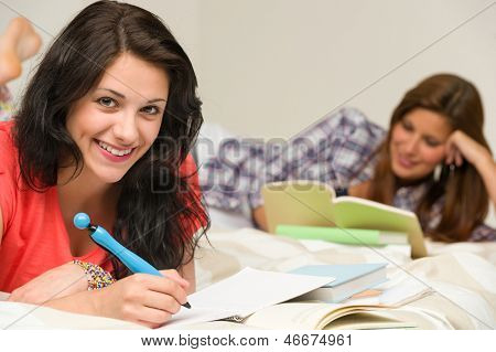 Smiling happy female students preparing for exam