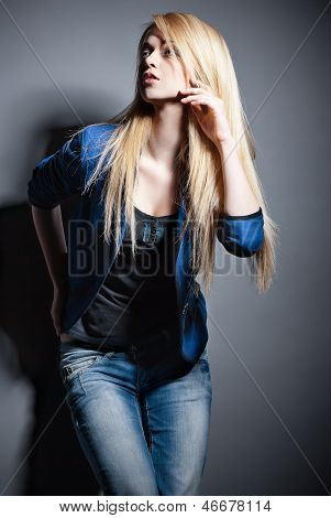 Posing blond woman with long hair on grey