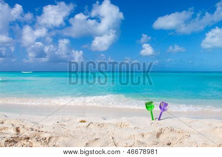 Couple Of Colored Spades On A White Sand Beach