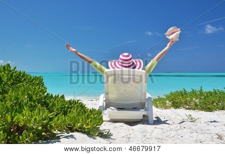 Girl with a shell on the sunbed looking to the ocean. Exuma, Bahamas