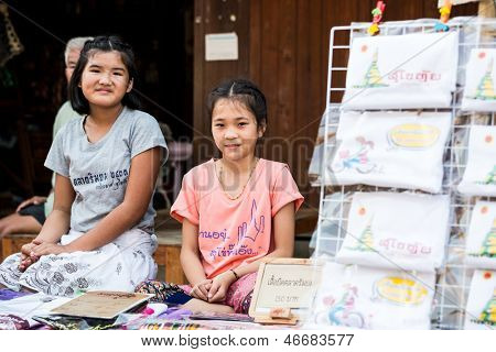 SUKHOTHAI, THAILAND - MAY 4: Unidentified girls are selling Thai traditional souvenir on May 4, 2013 at Rim Yom 2437 night market, Sukhothai, Thailand.