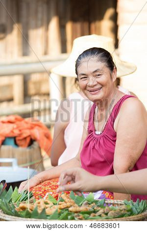 SUKHOTHAI, THAILAND - MAY 4: Unidentified mature woman is selling Thai traditional snack on May 4, 2013 at Rim Yom 2437 night market, Sukhothai, Thailand.