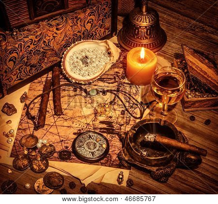 Closeup on beautiful buccaneer treasure background, luxury pirates alcohol drink, cigars, compass, pearl beads, drawing map, piracy lifestyle concept