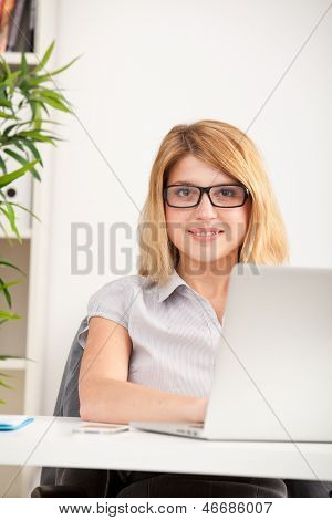 A young woman wearing glasses in front of a laptop sitting in the office