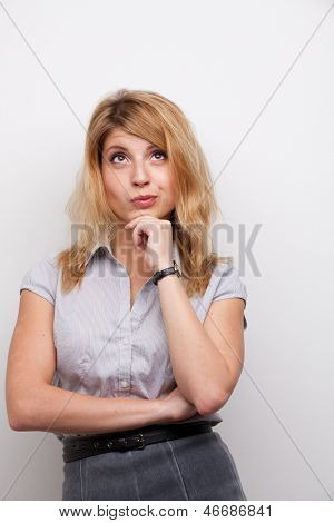 coquettish woman with the hand on her chin studio shot grey background
