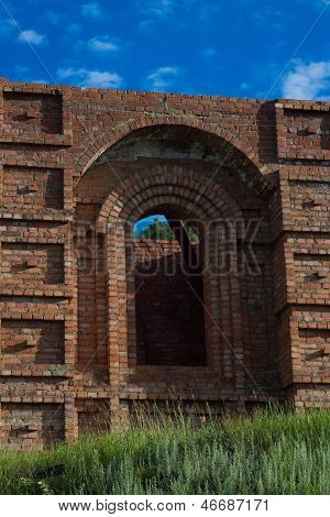 Unfinished church from a red brick grassed
