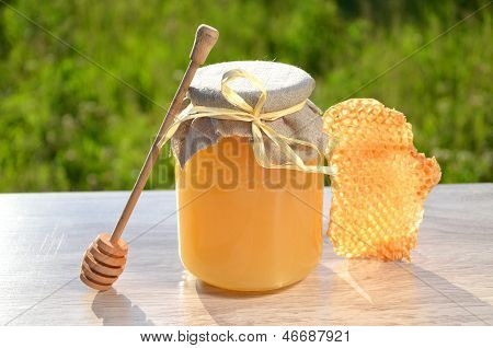 piece of honeycomb, honey dipper and jar full of delicious fresh honey in apiary