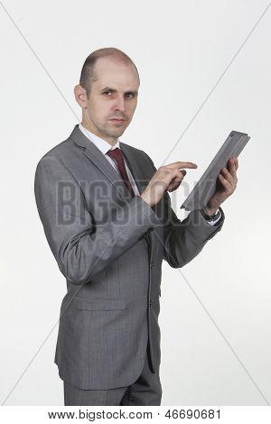 Smart Businessman Using A Handheld Tablet