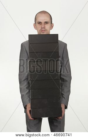 Businessman Carrying A Stack Of Black Boxes