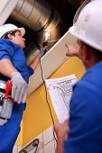 stock photo of exhaust pipes  - Two workers inspecting ventilation system - JPG