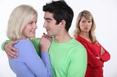 stock photo of adultery  - Jealous woman looking at a man hugging a young woman - JPG
