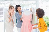 image of dress mannequin  - Attractive fashion designers looking at a dress on a mannequin - JPG