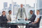 stock photo of cheers  - Cheerful team of business people in the meeting room with the boss standing in the middle - JPG