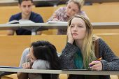 stock photo of boredom  - Demotivated students sitting in a lecture hall with one girl napping in college - JPG