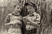 stock photo of toy phone  - Two young stylish boys browse the internet on mobile phone - JPG