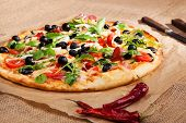 image of crust  - Fresh colorful round pizza with fresh herbs ham black olives and melted cheese on brown background - JPG