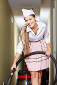 Happy cleaning lady with vacuum cleaner cleaning a hotel floor