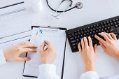 stock photo of prescription  - picture of doctor and nurse writing prescription paper - JPG