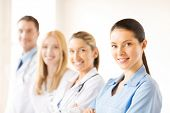 stock photo of surgeons  - attractive female doctor or nurse in front of medical group - JPG