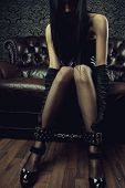 stock photo of latex woman  - Sexy gothic girl with legs in leg cuffs - JPG