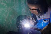foto of pipe-welding  - Welder in protective suit and mask welds metal pipes - JPG