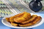 image of plantain  - Stack of fried sliced plantain bananas on plate with attractive traditional Mexican background - JPG