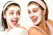 stock photo of headband  - Cheerful girls having facial mask and laughing at each other - JPG
