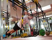 stock photo of rope pulling  - Crossfit fitness TRX push ups man workout at gym - JPG