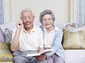 picture of korean  - senior asian couple reading a book together at home - JPG
