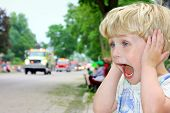 stock photo of parade  - A young blonde boy covers his ears and looks excited as ambulances and fire trucks drive by in a parade - JPG
