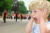 stock photo of school carnival  - A cute toddler boy covers his ears as he watches a school marching band walk by in a parade - JPG