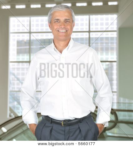 Middle Aged Businessman In White Shirt Hands In Pockets In Building