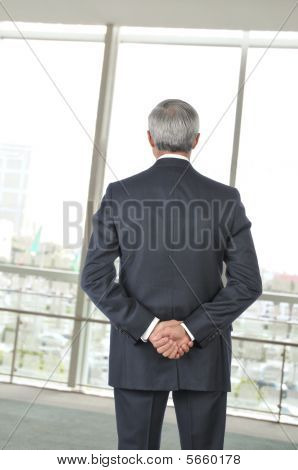 Smiling Middle Aged Businessman Standing In Office Setting With Coffee