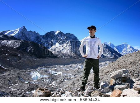 Hiker standing the Khumbu Valley with the Himalayan Mountain Range in background near Gorak Shep in the Sagarmatha (Mount Everest) National Park in Nepal