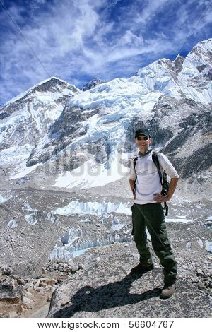 Man standing at Mount Everest Base Camp with the black rock pyramide of Mount Everest (8848m) in the background