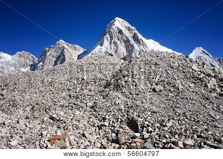 Pumori Mountain against blue sky. Pumori (or Pumo Ri) is a mountain on the Nepal-Tibet border in the Mahalangur section of the Himalaya. Pumori lies just eight kilometres west of Mount Everest