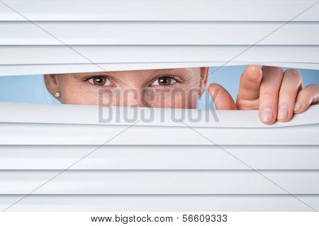 Woman Looking Through Closed Blinds