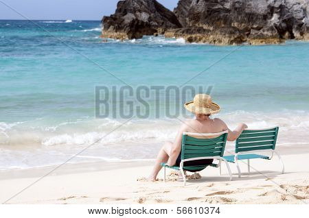Elderly woman sitting at the beach
