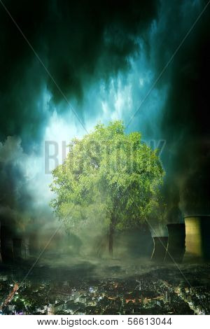 Concept picture of single green tree standing in an unhealthy and dark environment. The environment does look like a future city with dark clouds, smog and polluted air