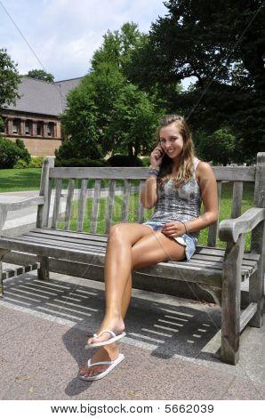 Teenage Girl Sitting On Bench With Phone