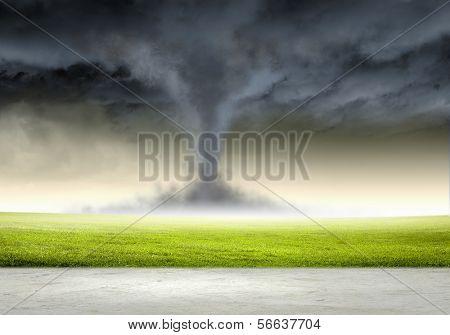 Image of powerful huge tornado twisting in meadow