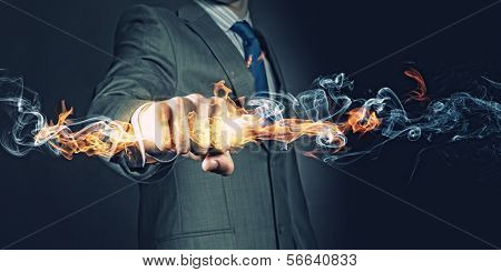 Businessman holding fire flames in fist. Power and control