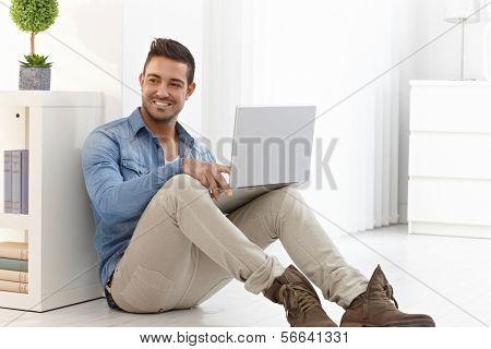 Glücklich junger Mann sitzt zu Hause, im Erdgeschoss mit Laptop-Computer.