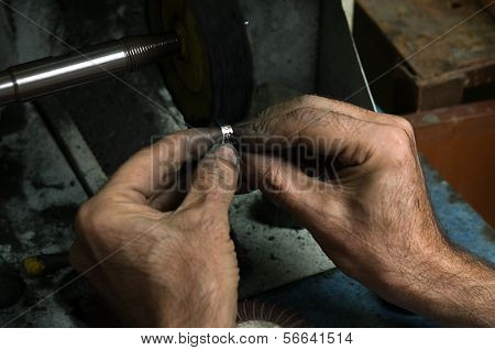 Goldsmith polishing silver ring with his old hands