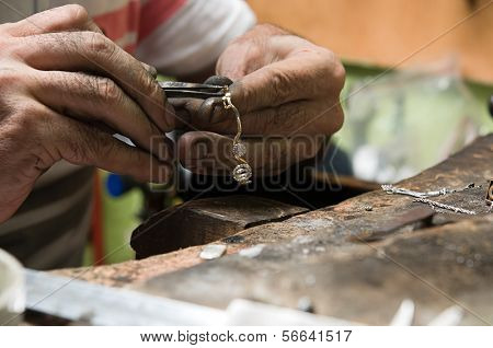 Goldsmith working on a silver necklace with his aged hands