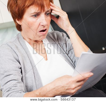 Elderly woman reading a letter at home. Sad businesswoman with document
