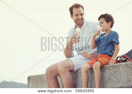 Father and son eating ice cream together at the beach on vacation having fun with melting mess