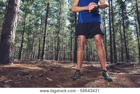 Man looking at stopwatch to check gps pace and time on trail run