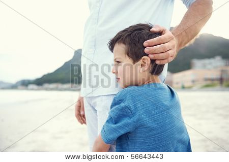 Son hugging fathers leg at beach feeling safe and love